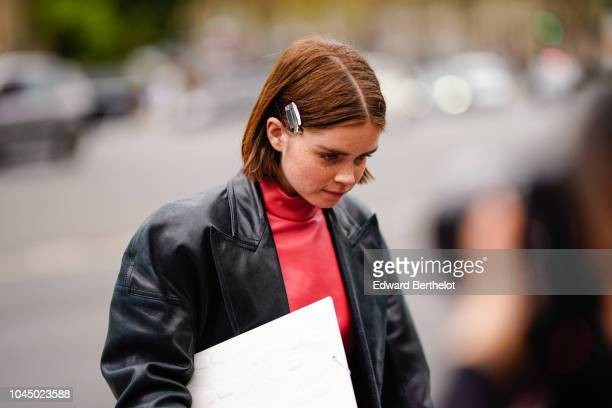 Reese Blutstein wears a black leather jacket a red dress outside Miu Miu during Paris Fashion Week Womenswear Spring/Summer 2019 on October 2 2018 in...