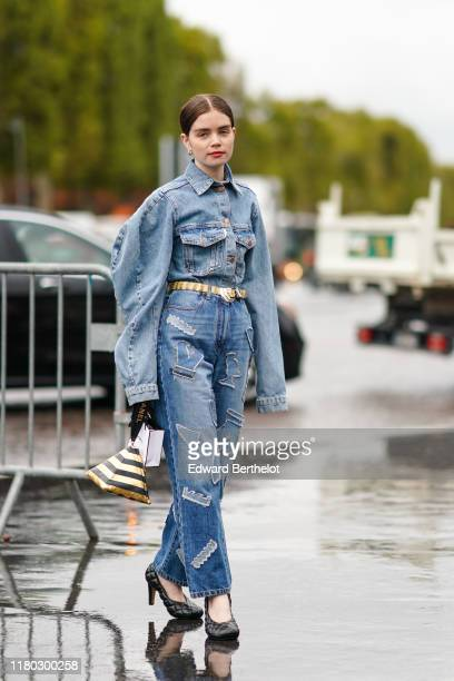 Reese Blutstein wears a blue denim oversized jacket with large pockets a belt blue denim jeans with patches a golden and black striped pyramid bag...