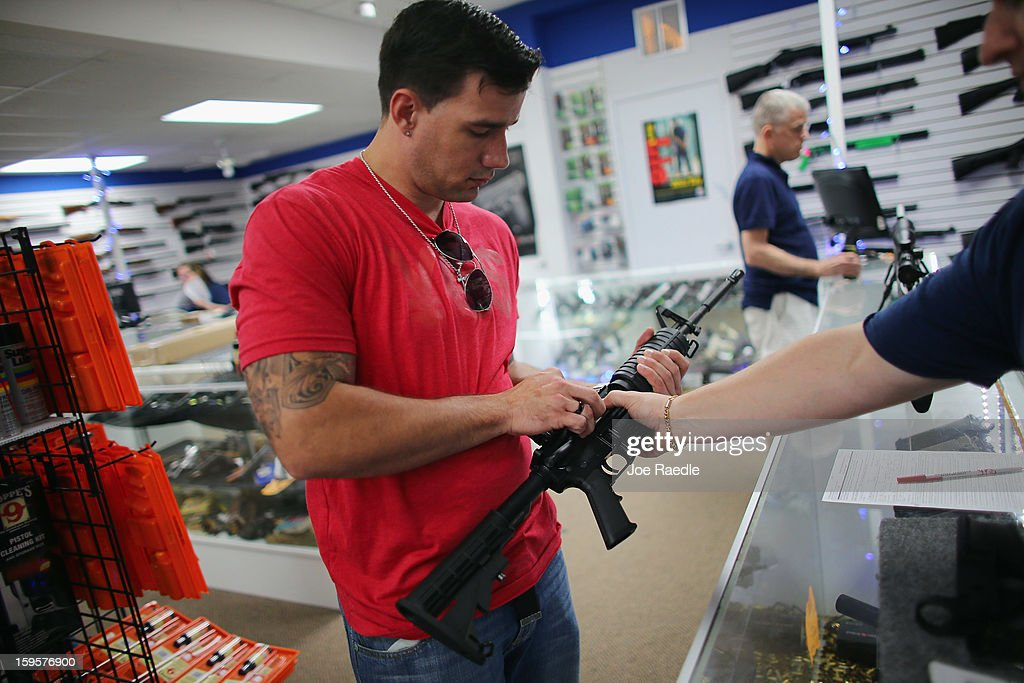 Reese Magnant (L) is helped by Jonathan Schwartz , a salesman at the National Armory gun store, as he looks to buy a National Armory AR-15 Battle Entry Assault Rifle on January 16, 2013 in Pompano Beach, Florida. President Barack Obama today in Washington, DC announced a broad range of gun initiatives that his administration thinks will help curb gun violence.