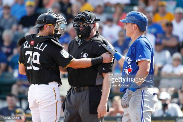 Reese McGuire of the Toronto Blue Jays and Francisco Cervelli of the Pittsburgh Pirates tend to home plate umpire Paul Emmel after he was hit by...