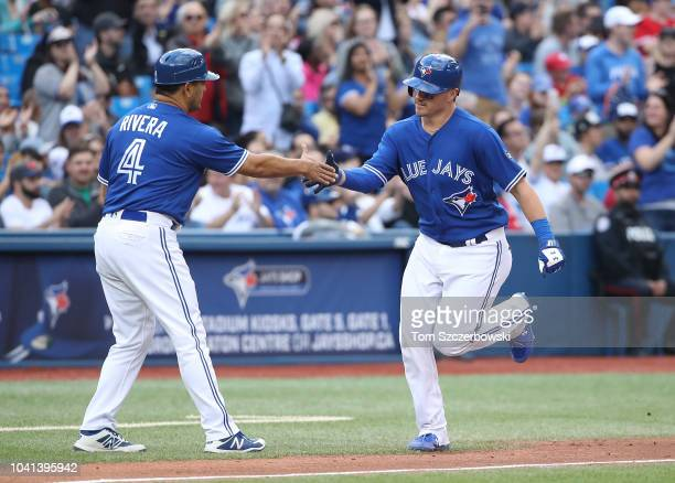 Reese McGuire of the Toronto Blue Jays is congratulated by third base coach Luis Rivera after hitting a solo home run in the fifth inning during MLB...