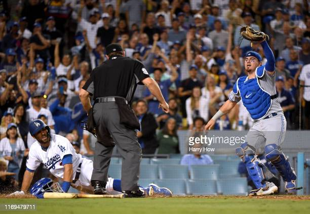 Reese McGuire of the Toronto Blue Jays reacts to umpire Brian Knight after tagging out Chris Taylor of the Los Angeles Dodgers attempting to stretch...