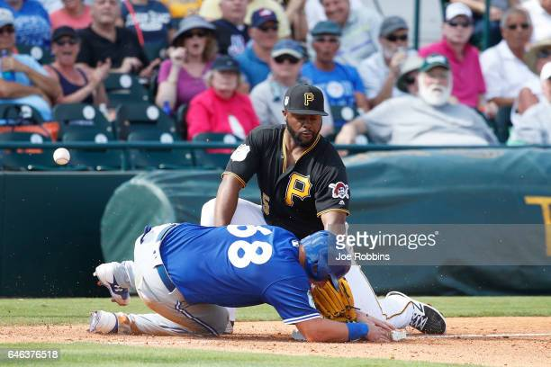 Reese McGuire of the Toronto Blue Jays slides safely at third base ahead of the throw to Jason Rogers of the Pittsburgh Pirates in the sixth inning...