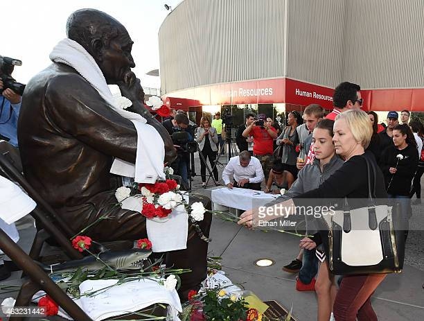 Reese Rivera and her mother former UNLV student Ellen Rivera place carnations at a statue of Jerry Tarkanian outside the Thomas Mack Center at UNLV...