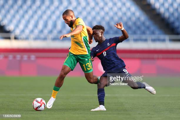 Reeve Frosler of Team South Africa battles for possession with Nathanael Mbuku of Team France during the Men's First Round Group A match between...
