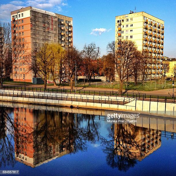 refection of buildings in calm river - pomorskie province stock photos and pictures