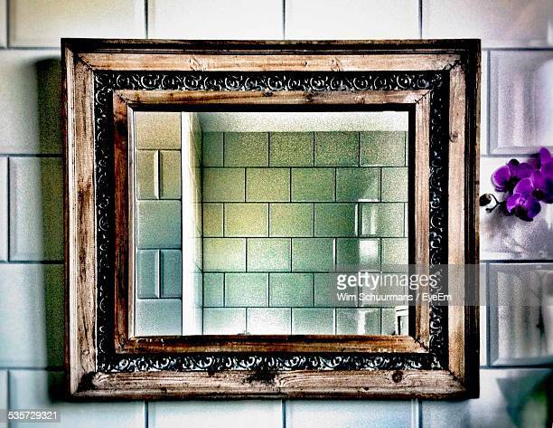 refection of tiled wall in mirror at home - mirror frame stock photos and pictures