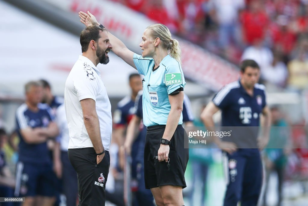Refeere Bibiana Steinhaus argues with Stefan Ruthenbeck Head Coach of 1. FC Koeln as he is send out during the Bundesliga match between 1. FC Koeln and FC Bayern Muenchen at RheinEnergieStadion on May 5, 2018 in Cologne, Germany.
