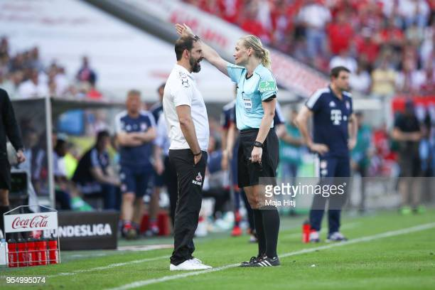 Refeere Bibiana Steinhaus argues with Stefan Ruthenbeck Head Coach of 1 FC Koeln as he is send out during the Bundesliga match between 1 FC Koeln and...
