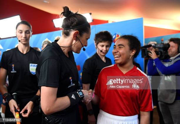 Refere Kate Jacewicz shakes hands with a mascot in the tunnel prior to the 2019 FIFA Women's World Cup France group A match between Norway and...