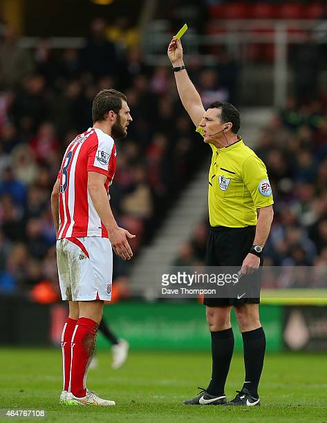 Refere Neil Swarbrick shows a yellow card to Erik Pieters of Stoke City during the Barclays Premier League match between Stoke City and Hull City at...