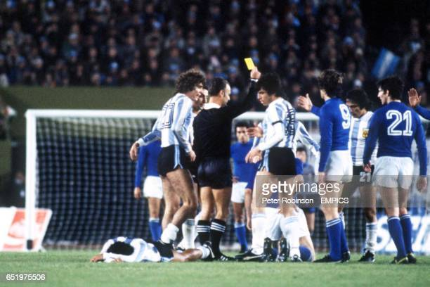 Referee Abraham Klein hands out a caution as Argentina's Alberto Tarantini and Daniel Passarella crowd him