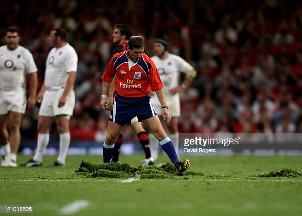 Referee Alain Rolland of Ireland repairs the damaged pitch during the rugby union international friendly match between Wales and England at the...