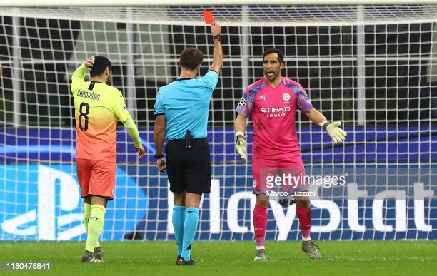 Referee Alaksei Kulbakov shows the red card to Claudio Bravo of Manchester City during the UEFA Champions League group C match between Atalanta and...
