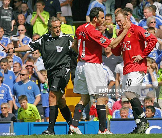 Referee Alan Wiley looks on as Manchester United's Wayne Rooney is checked by concerned team mate and Captain, Welsh player Ryan Giggs after Rooney...
