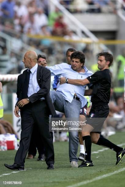 Referee Alberto Rizzoli holds Silvio Baldini head coach of Parma Calcio while kicking Domenico Di Carlo head coach of Catania Calcio during the Serie...