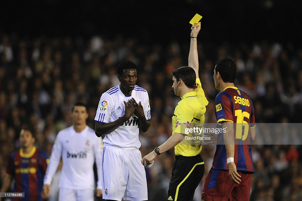 Referee Alberto Undiano Mallenco shows the yellow card to Adebayor of Real Madrid (L) during the Copa del Rey Final between Real Madrid and Barcelona at Estadio Mestalla on April 20, 2011 in Valencia, Spain.