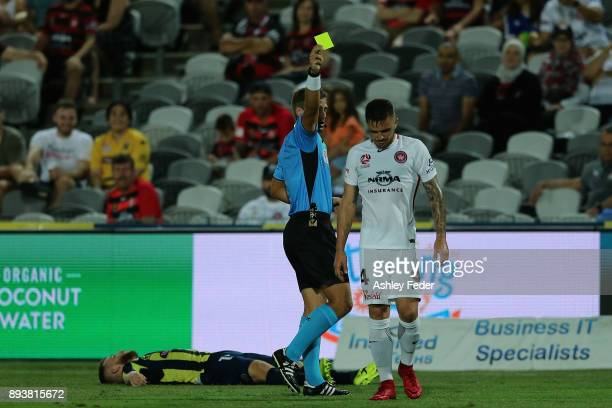 Referee Alex King issues a yellow card to Josh Risdon of the Wanderers during the round 11 ALeague match between the Central Coast and the Western...