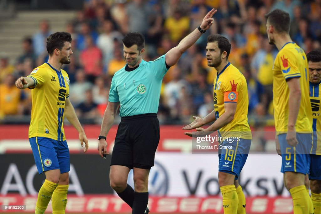 Referee Alexander Sather (2nd L) argues with players of Braunschweig during the Second Bundesliga match between Eintracht Braunschweig and DSC Arminia Bielefeld at Eintracht Stadion on April 20, 2018 in Braunschweig, Germany.