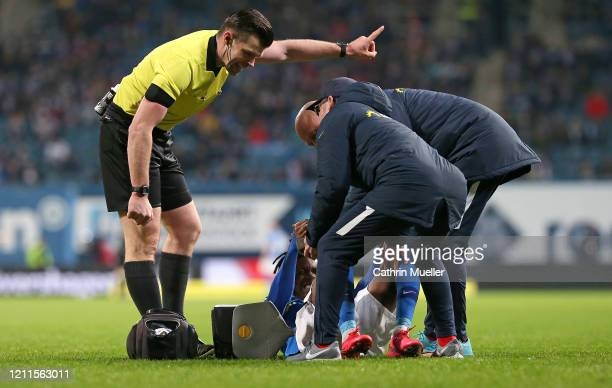 Referee Alexander Sather direct the medical team and Aaron Opoku of Hansa Rostock to leave the pitch during the 3 Liga match between Hansa Rostock...