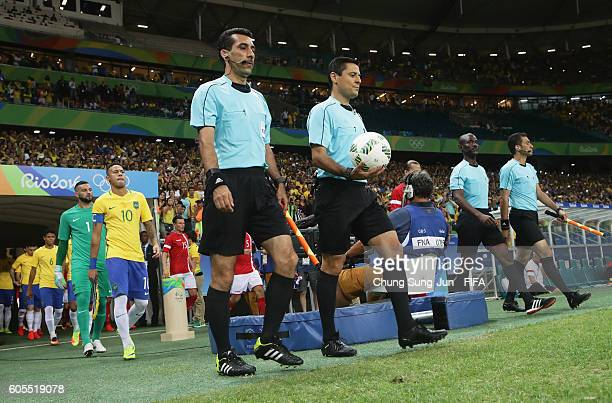 Referee Alireza Faghani assistant referees Reza Sokhandan and Mohammadreza Mansouri and 4th official Joseph Lamptey walk out for the Men's Football...