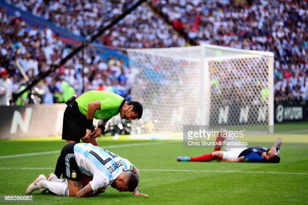 Referee Alireza Faghani checks on Nicolas Otamendi of Argentina as Olivier Giroud of France lies injured during the 2018 FIFA World Cup Russia Round...