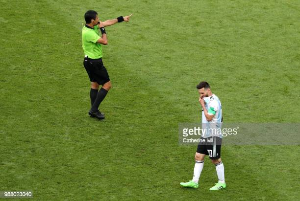 Referee Alireza Faghani gives instructions as Lionel Messi of Argentina looks dejected during the 2018 FIFA World Cup Russia Round of 16 match...