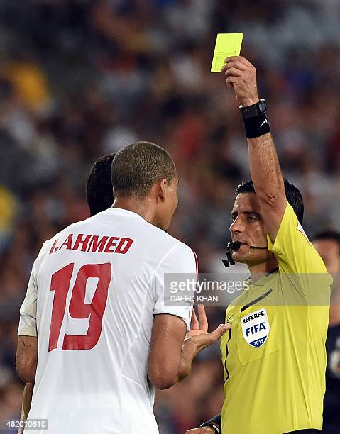 Referee Alireza Faghani of Iran gives a yellow card to Ismail Ahmed of the United Arab Emirates during the quarterfinal football match between Japan...