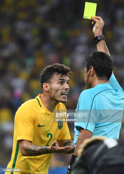 Referee Alireza Faghani of Iran shows Zeca of Brazil the yellow card during the Men's soccer Gold Medal Match between Brazil and Germany during the...