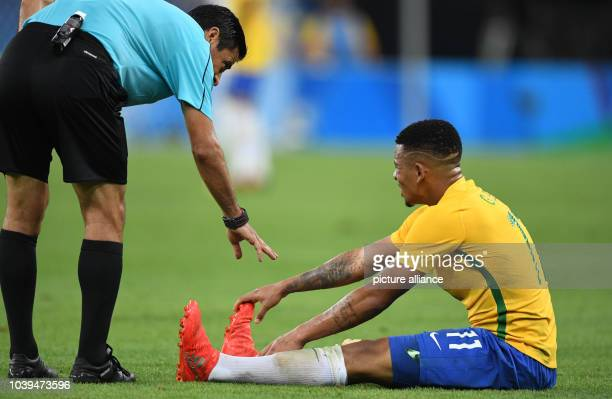 Referee Alireza Faghani of Iran speaks Gabriel Jesus of Brazil who sits on the floor after a foul during the Men's soccer Gold Medal Match between...