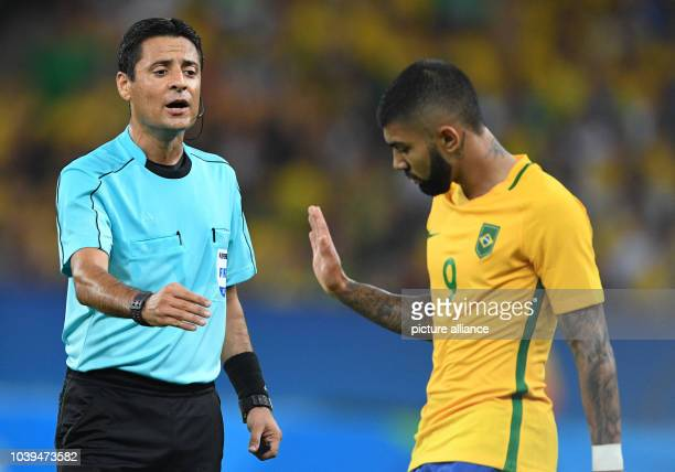 Referee Alireza Faghani of Iran warns Gabriel Barbosa of Brazil vie for the ball during the Men's soccer Gold Medal Match between Brazil and Germany...
