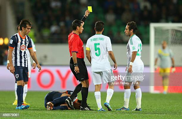 Referee Alireza Faghani shows a yellow card to Adil Karrouchy of Raja Casablanca during the FIFA Club World Cup Quarter Final match between Raja...