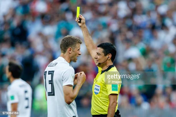 referee Alireza Faghani shows a yellow card to Thomas Mueller of Germany during the 2018 FIFA World Cup Russia group F match between Germany and...