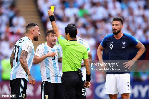 Referee Alireza Faghani shows Nicolas Tagliafico of Argentina a yellow card during the 2018 FIFA World Cup Russia Round of 16 match between France...
