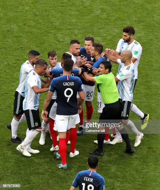 Referee Alireza Faghani tries to divide Argentina and France players during the 2018 FIFA World Cup Russia Round of 16 match between France and...