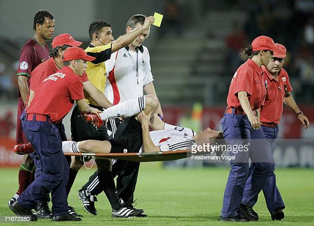 Referee Alon Yefet gives the injured Lukas Sinkiewicz of Germany the yellow card during the UEFA U21's Championship Group A match between Germany and...
