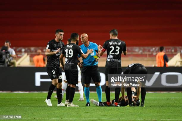 Referee Amaury Delerue with Umut Bozok and Clement Depres of Nimes during the Ligue 1 match between AS Monaco and Nimes at Stade Louis II on...