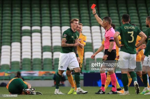 Referee Anastasios Sidiropoulos shows a red card to Republic of Ireland's midfielder James McClean for his challenge on Wales' midfielder Ethan...