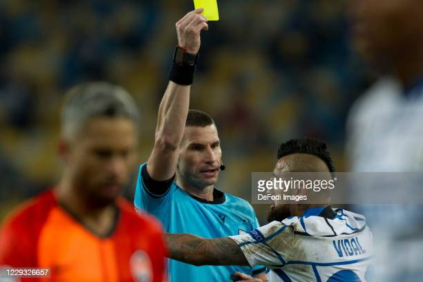 Referee and Arturo Vidal of Internazionale shows the yellow card during the UEFA Champions League Group B stage match between Shakhtar Donetsk and FC...