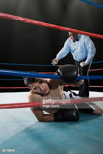 Referee and boxer on floor