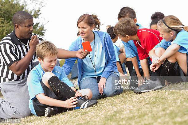 referee and coach helping injured soccer player during kids' game - female umpire stockfoto's en -beelden