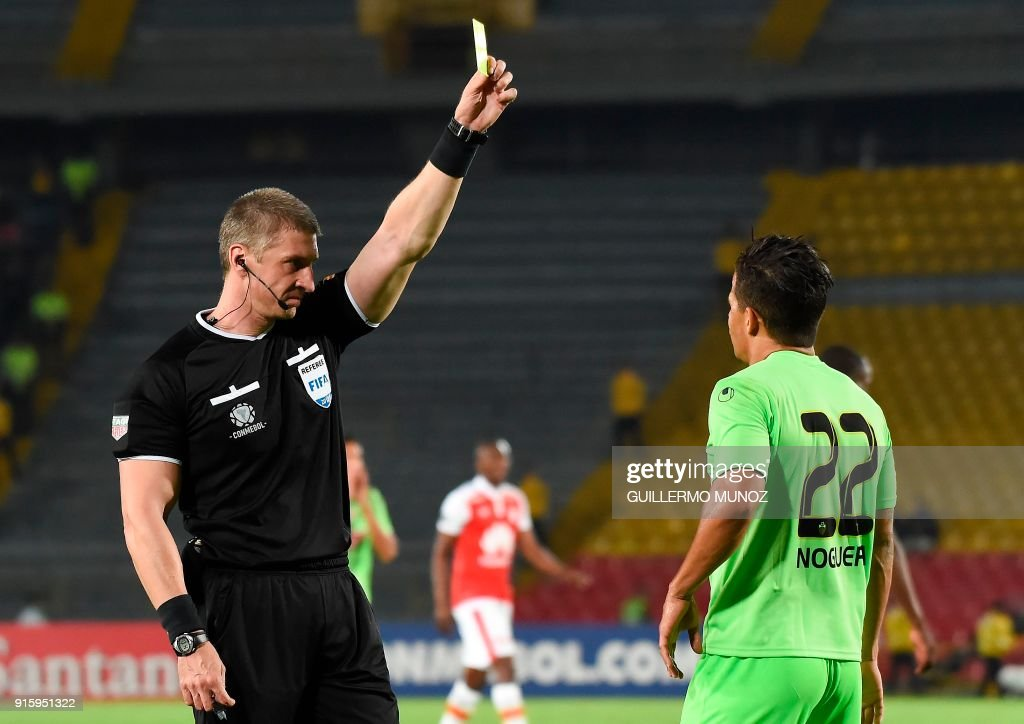 Referee Anderson Daronco (L) of Brazil shows the yellow card to Venezuela's Tachira player Hector Emilio Noguera Sanchez during their copa Libertadores football match against Colombia's Santa Fe at El Campin stadium in Bogota on February 8, 2018. /