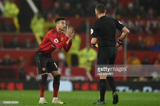 Referee Andre Mariner shows a yellow card to Manchester United's English midfielder Jesse Lingard during the English Premier League football match...