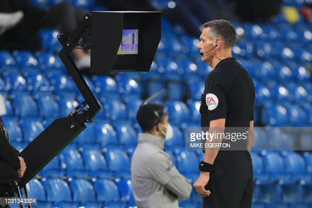 Referee Andre Marriner checks VAR during the English Premier League football match between Leeds United and Southampton at Elland Road in Leeds,...