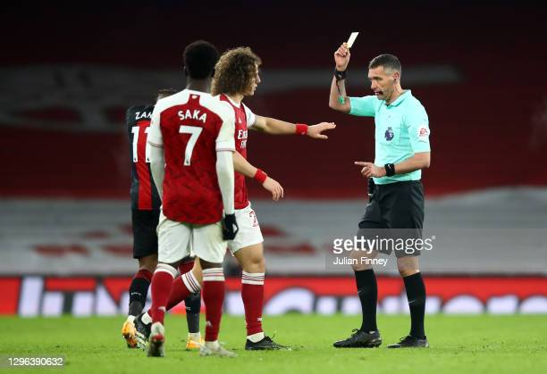Referee Andre Marriner gives David Luiz of Arsenal a yellow card during the Premier League match between Arsenal and Crystal Palace at Emirates...