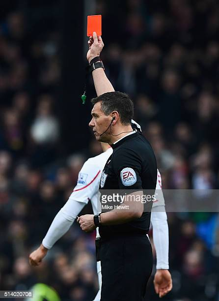 Referee Andre Marriner shows a red card to James Milner of Liverpool as he is sent off during the Barclays Premier League match between Crystal...