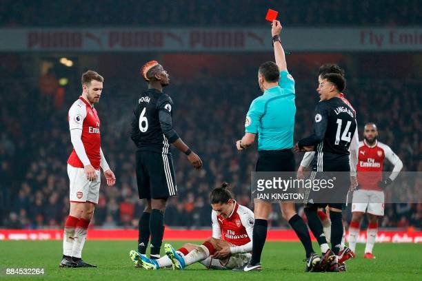Referee Andre Marriner shows a red card to Manchester United's French midfielder Paul Pogba for his challenge on Arsenal's Spanish defender Hector...