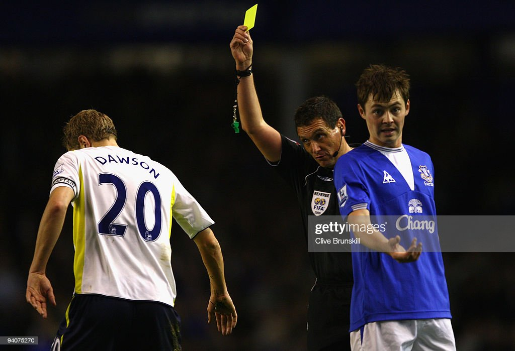 Referee Andre Marriner shows a yellow card to Michael Dawson of Tottenham Hotspur during the Barclays Premier League match between Everton and Tottenham Hotspur at Goodison Park on December 6, 2009 in Liverpool, England.