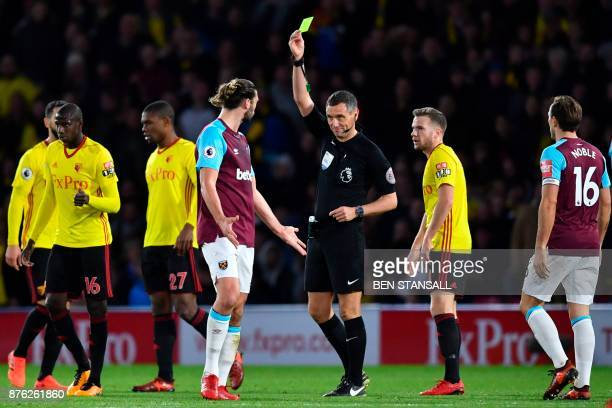 Referee Andre Marriner shows a yellow card to West Ham United's English striker Andy Carroll after an offtheball incident involving Carroll and...