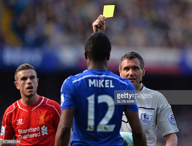 Referee Andre Marriner shows Chelsea's Nigerian midfielder John Obi Mikel a yellow warning card as Liverpool's English midfielder Jordan Henderson...